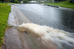 A photo of fast flowing water exiting from a residential storm-water drain during heavy rain.