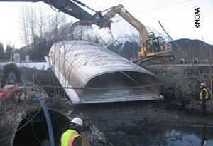 Installing a culvert. Salmon habitat restoration in Alaska.