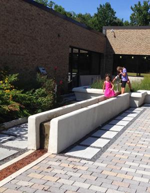 Children pump water along concrete flume
